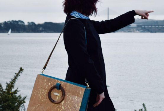 Bossy green cork business bag carried with the bi-coloured shoulder strap over the shoulder of a girl dresses in black, pointing with her finger at the ocean