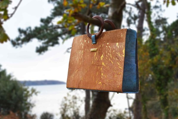Bossy natural-gold and green coloured cork, hanging with the round wood handles over a tree branch in front of the sea