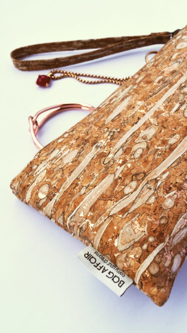 Wristlet of fennel and cork from Bag Affair in a detail view open with jewellery in rose-gold