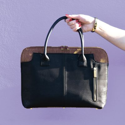 Savvy laptop bag for women in black and brown cork, hold by a hand in front of a purple wall