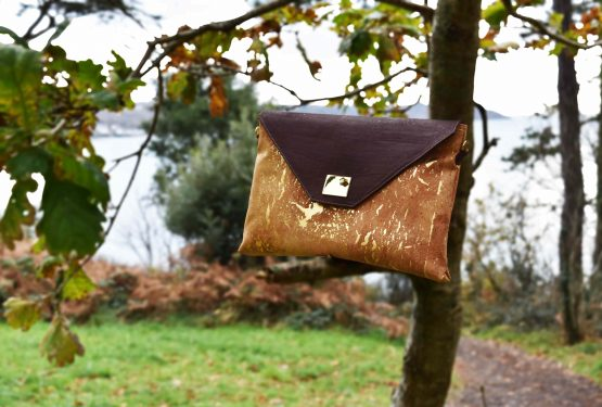 Sassy business bag gold-natural and brown cork placed on a branch of a tree in front of nature and ocean