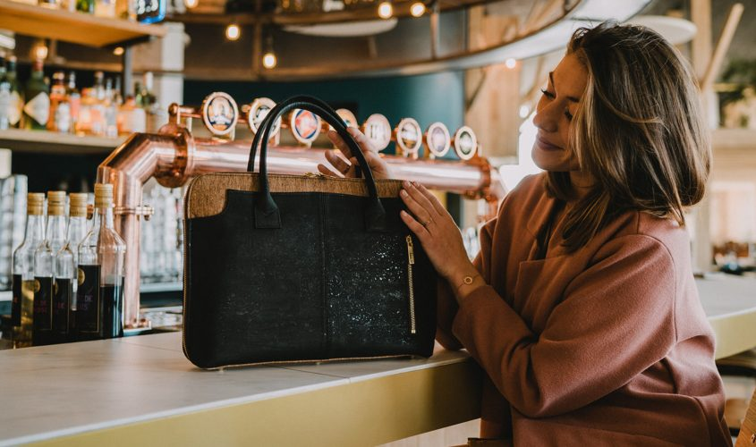 Business bag Savvy on a bar, hold and touched by a model in pink coat