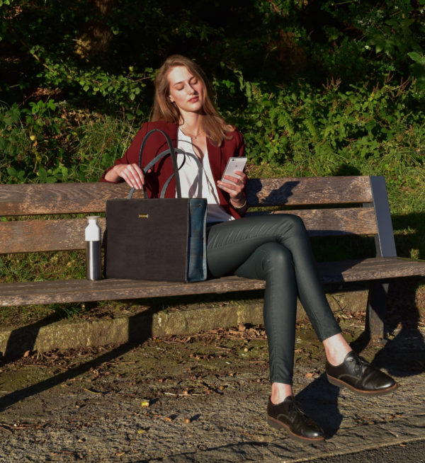 Model on a bench in nature with Classy business bag in black and green left of her