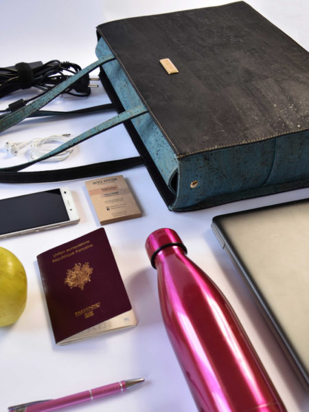 Classy business bag lying with bag content around like computer, bottle, phone, pen, apple, passport and charger