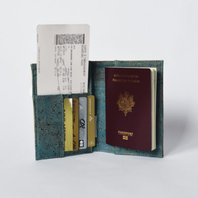 Passport cover open view, inner side green cork, holding a passport, boarding pass and cards, white background